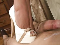 Naughty biotch is penalizing his giant schlong with her nasty heels and sexy boots